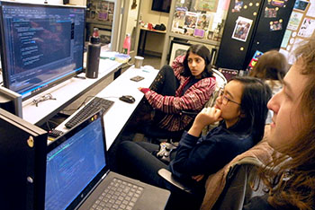 DFL students review programming code shown on a monitor